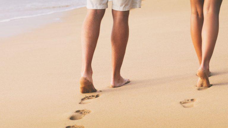 Nainen ja mies kävelevät rannalla