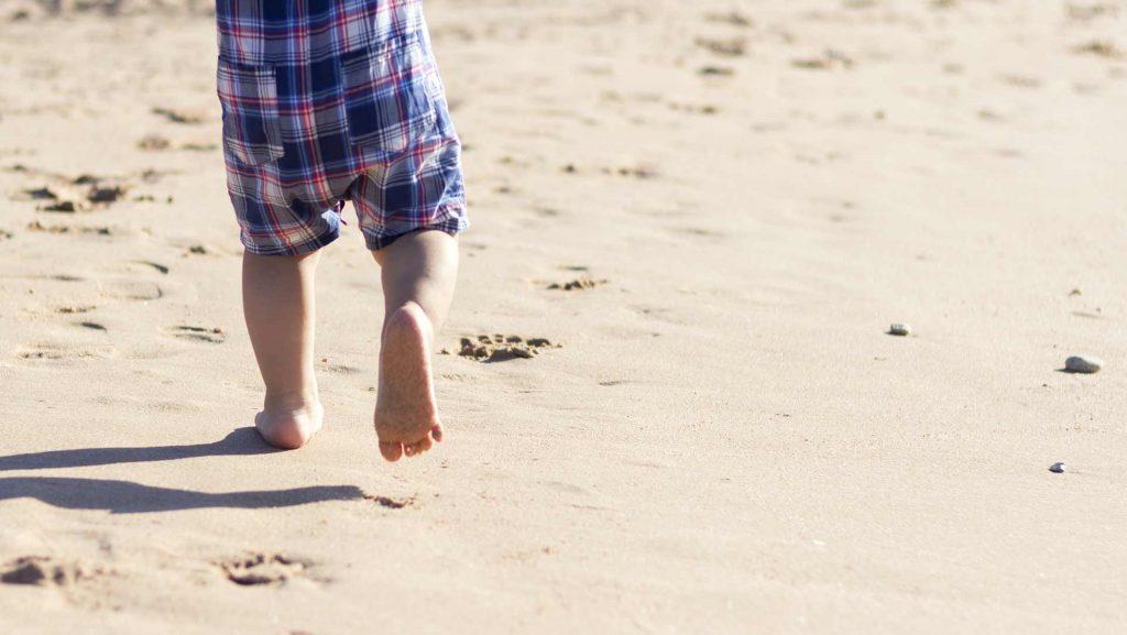 Lapsi juoksemassa hiekassa