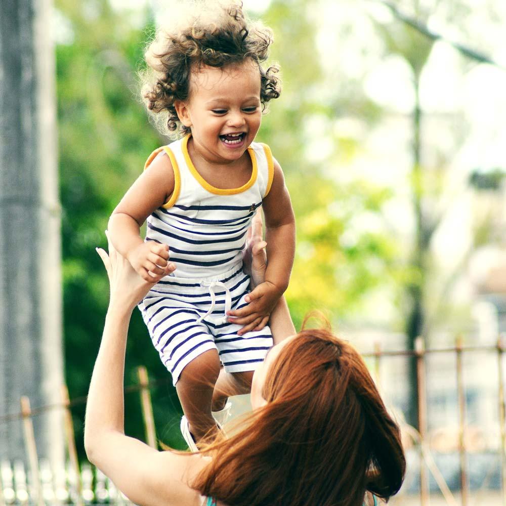 Nainen heittää lapsen ilmaan kevyesti