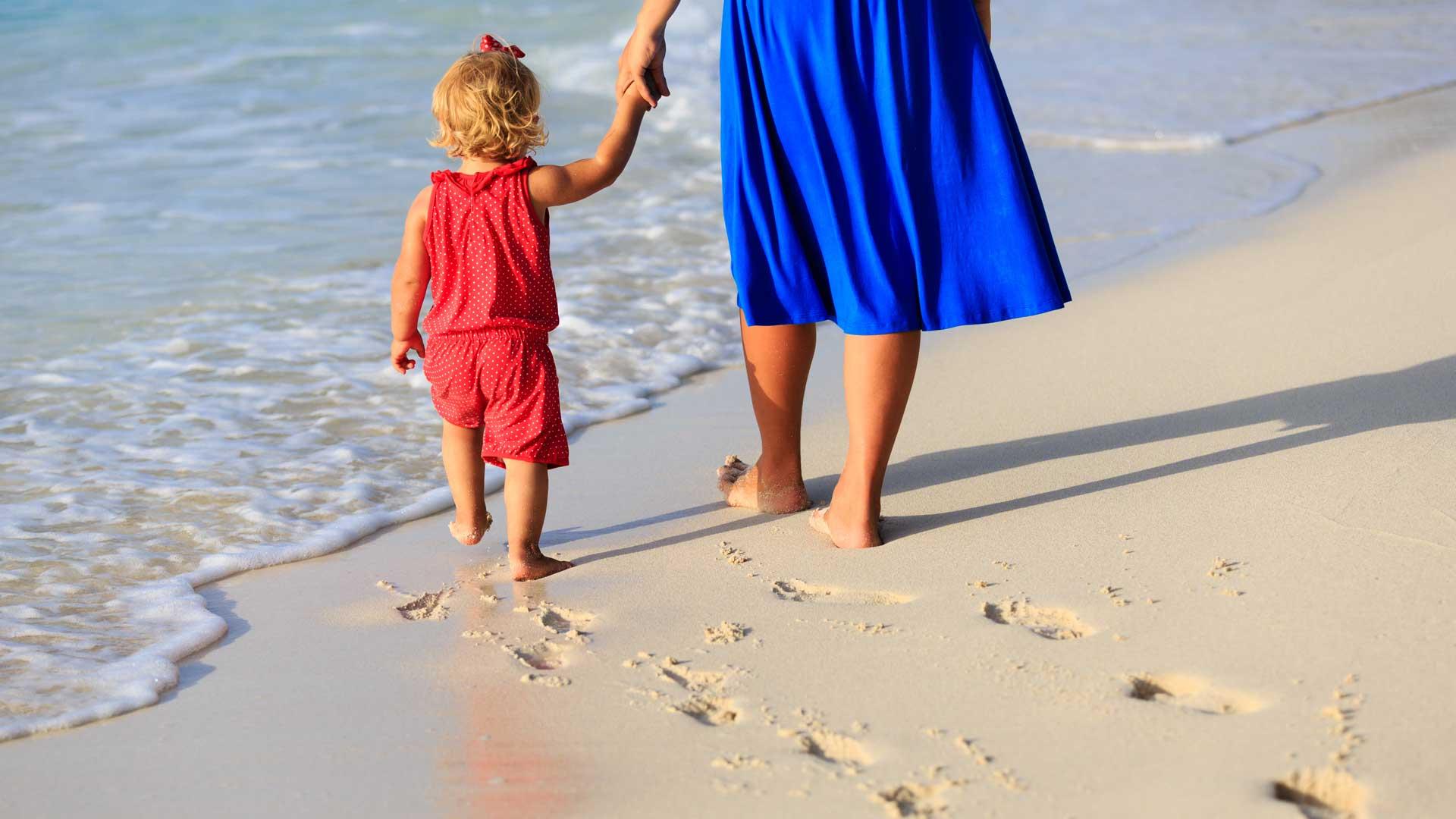 Äiti ja lapsi hiekkarannalla kävelemässä kohti vettä, jättäen hiekkaan jalanjälkiä