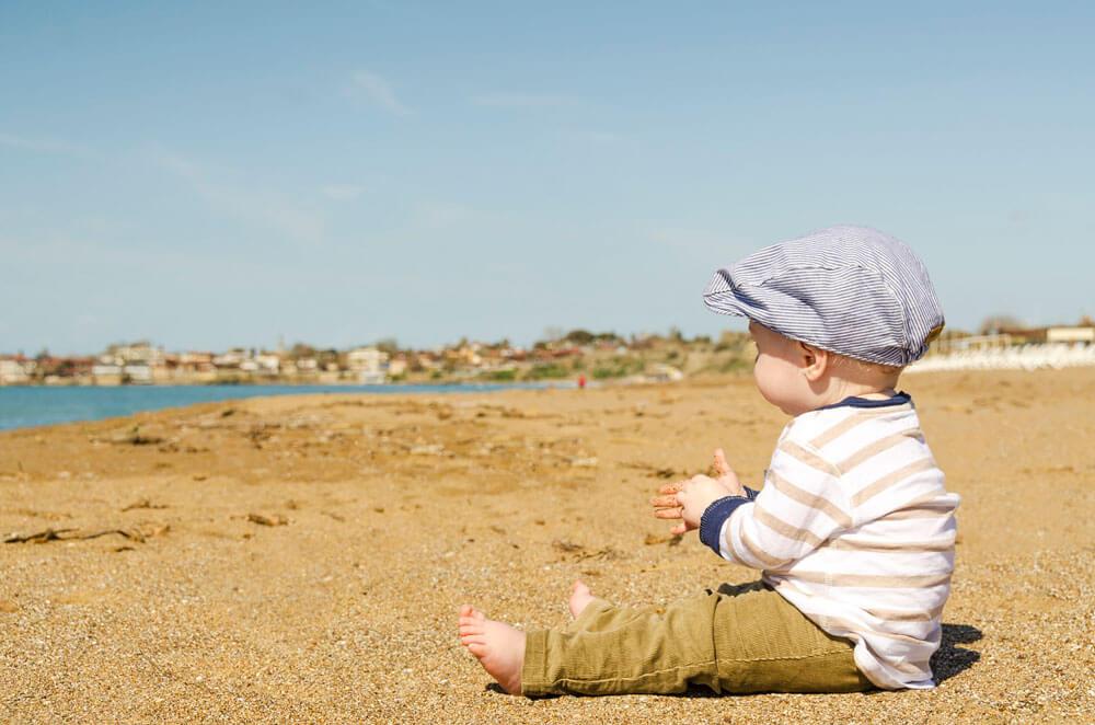 Vauva istumassa hiekarannalla katsoen kohti vettä