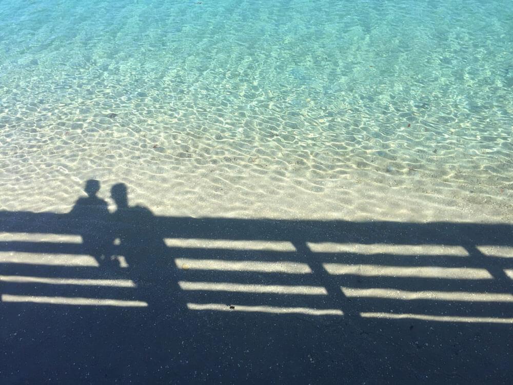 Kuva vedestä, jossa varjo kaiteesta ja kahdesta henkilöstä