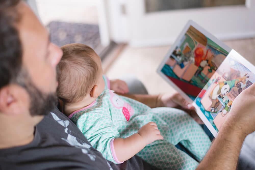 Mies lukee lasten kirjaa vauvalle