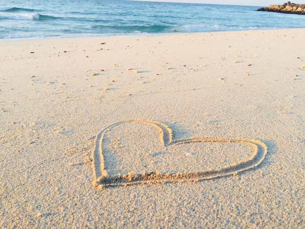 Kuvassa on hiekkaranta, johon on piirretty sydän