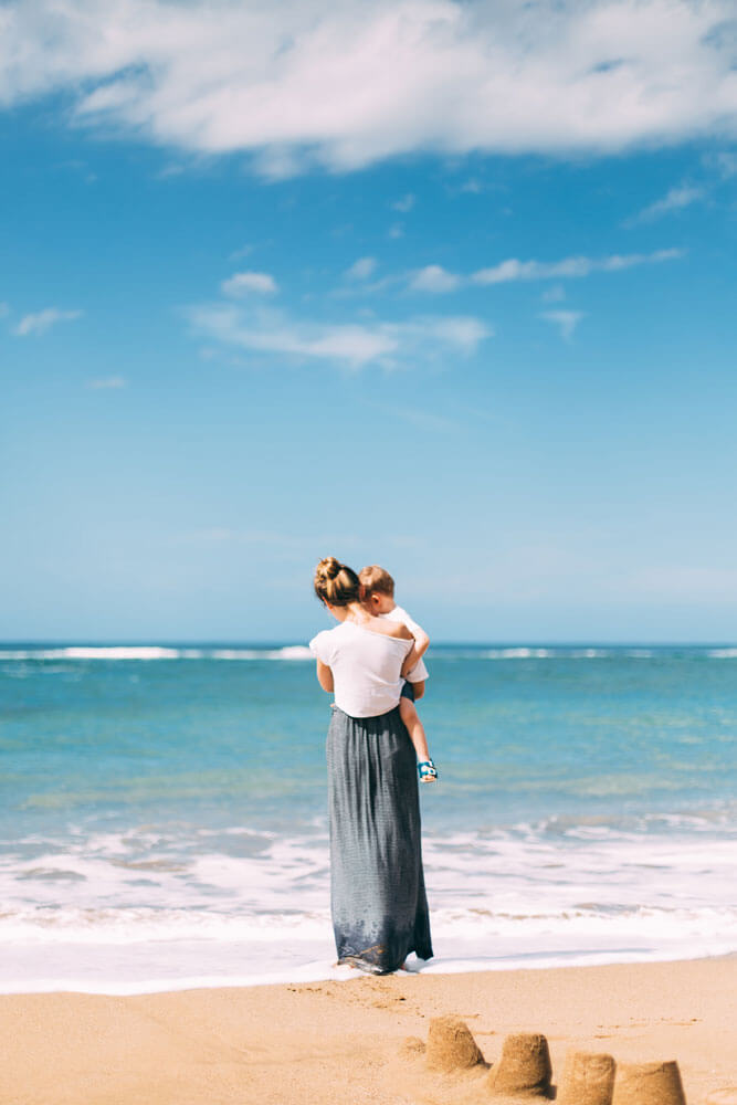 Kuvassa nainen pitelee lasta hiekkarannalla katsoen alaspäin vettä, joka osuu jalkoihin
