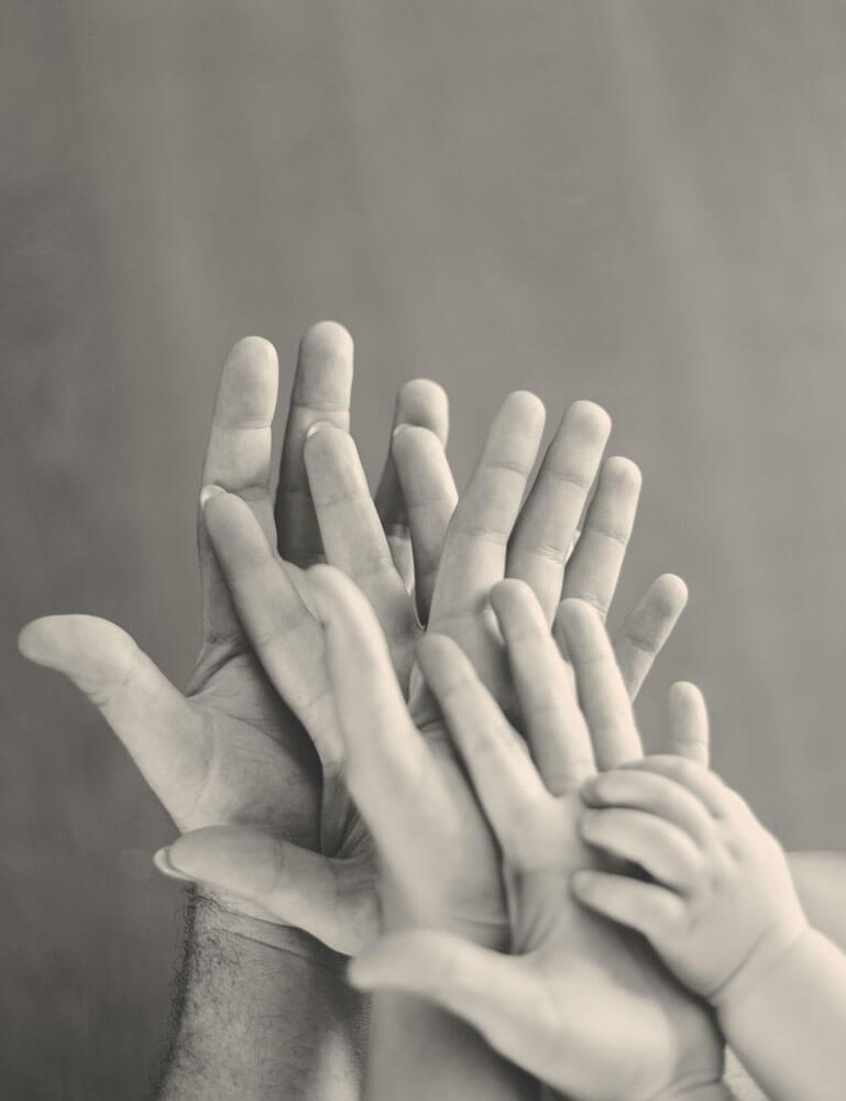 Kolme kättä päällekkäin ja vauvan käsi päälimmäisenä
