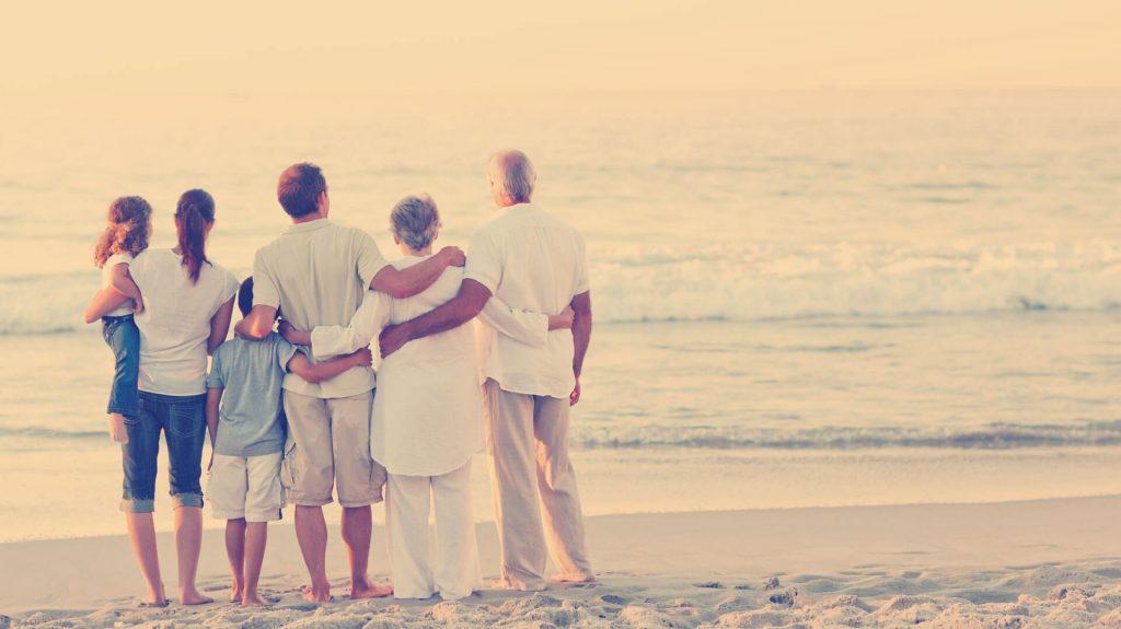 Kuvassa neljä aikuista ja kaksi lasta seisovat kädet toistensa olkapäillä katsellen merta.