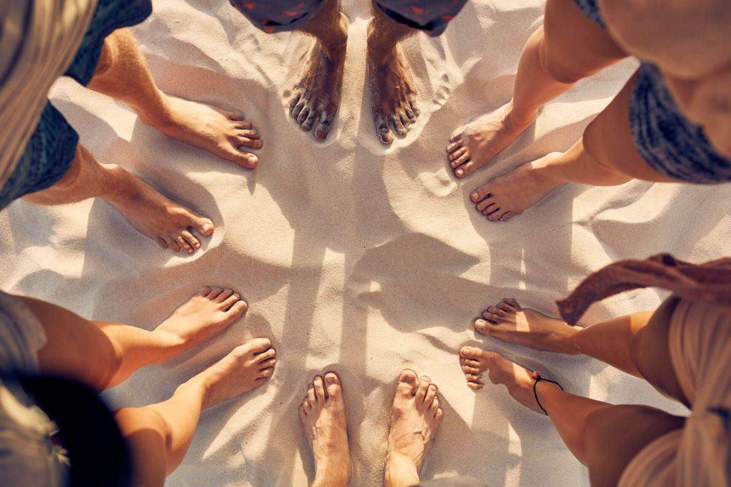 Kuvassa on ihmisiä seisomassa ympyrässä varpaat hiekassa