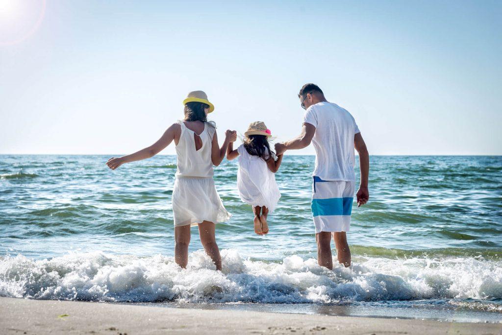 Kuvassa on kolmihenkinen perhe rannalla