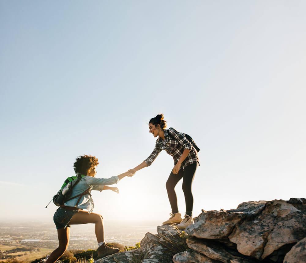 Nainen auttaa toista naista kiipeämään kiviä ojentaen kätensä