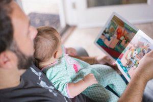 Kuvassa on mies, joka lukee vauvalle lastenkirjaa