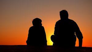 Kuvassa miehen ja lapsen hahmot istuvat auringonlaskua katsellen