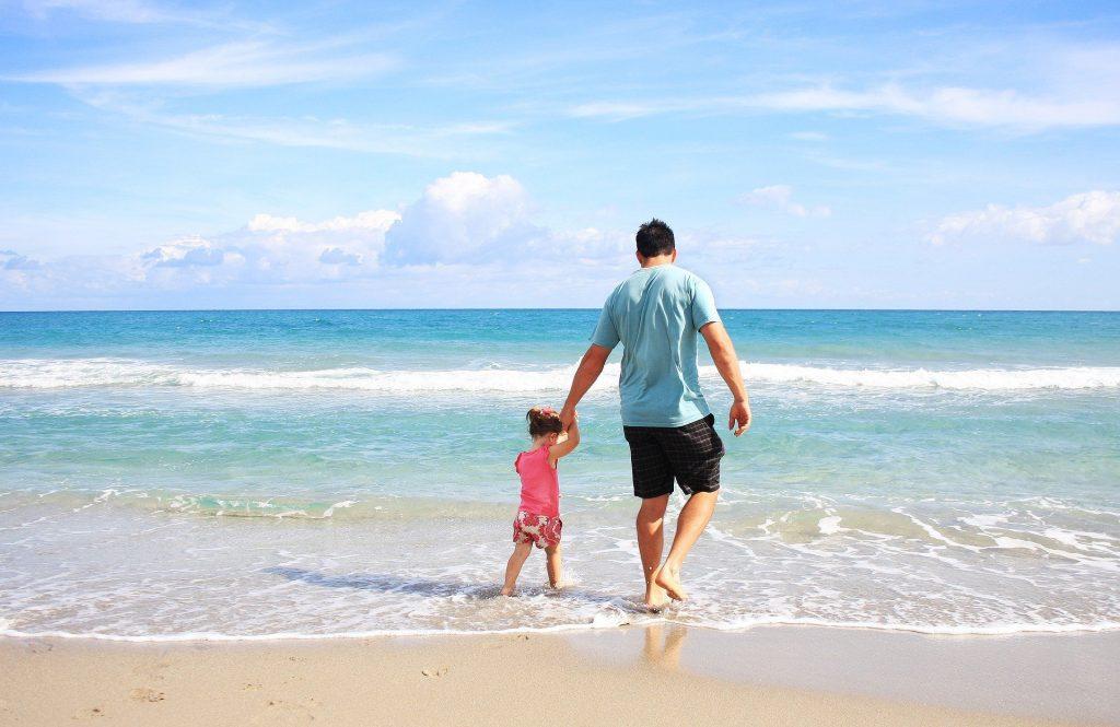 Kuvassa on mies ja lapsi kävelemässä rannalla
