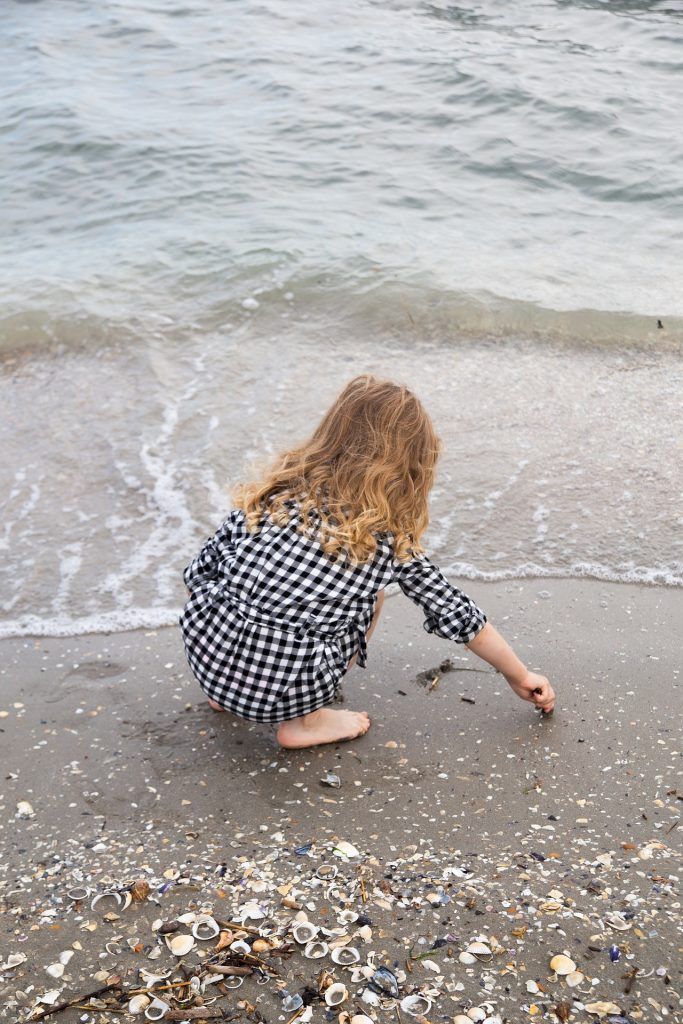 Kuvassa on pieni tyttö kyykyssä rannalla
