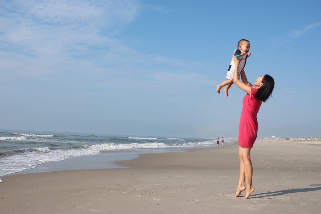 Kuvassa on nainen ja vauva rannalla. Nainen nostaa lasta ilmaan.
