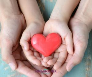 Kädet yhdessä, käsien välissä sydän, Helminauha-hankkeen logo.