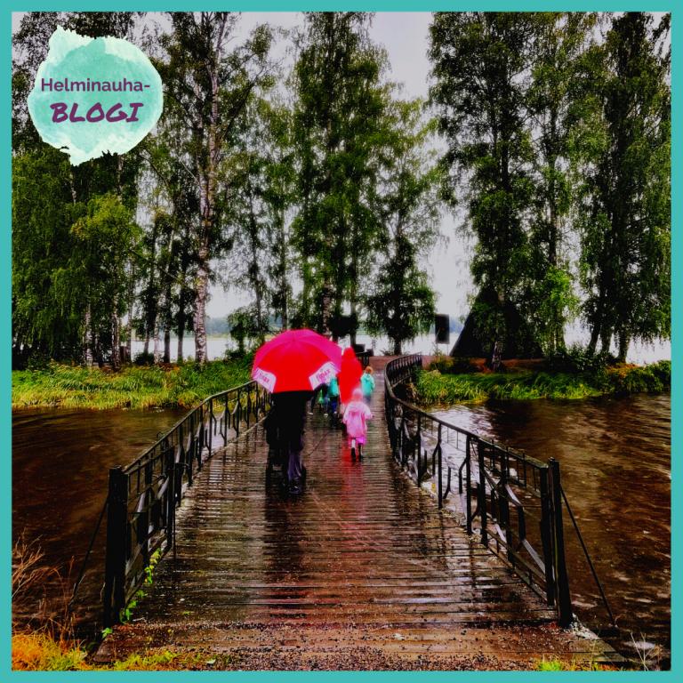 Henkilöitä kävelee sateessa sillalla, punainen sateenvarjo.